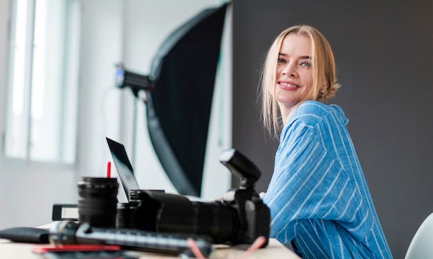 Smiley photographer woman sitting at her desk