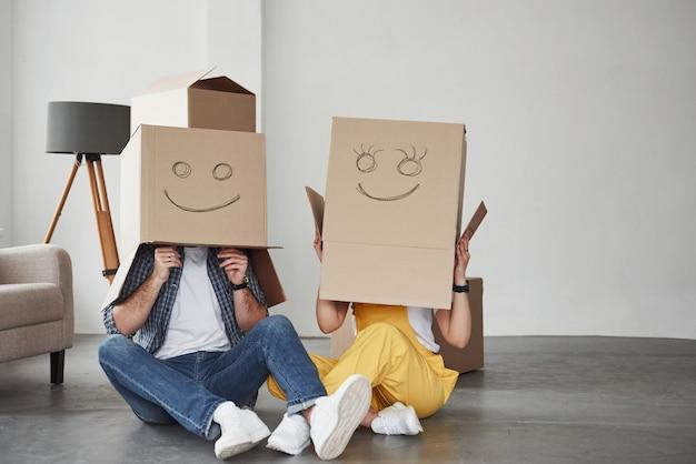 ボックスにスマイリー写真。彼らの新しい家で一緒に幸せなカップル。引っ越しの発想