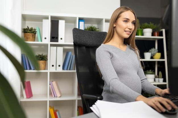 컴퓨터에서 작업하는 사무실에서 웃는 임신 사업가