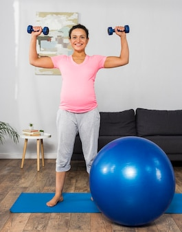Smiley pregnant woman exercising at home with weights and ball