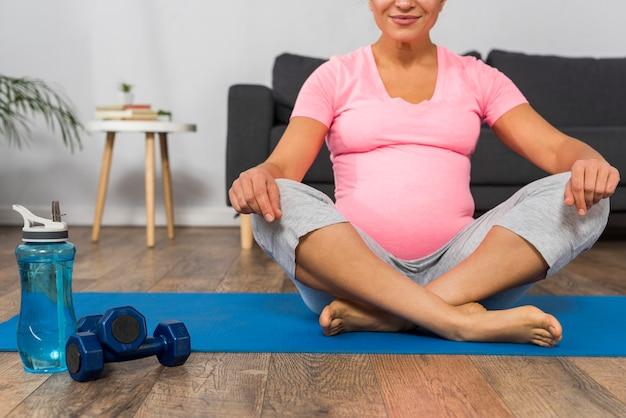 Donna incinta di smiley sull'esercitazione della stuoia a casa con i pesi e la bottiglia d'acqua