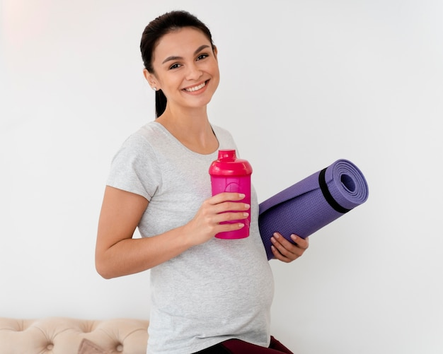 Smiley pregnant woman holding a fitness mat and a bottle of water