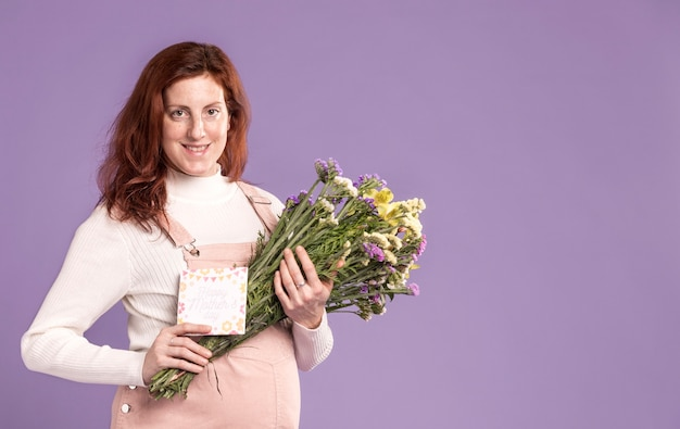 Smiley pregnant woman holding flowers bouquet