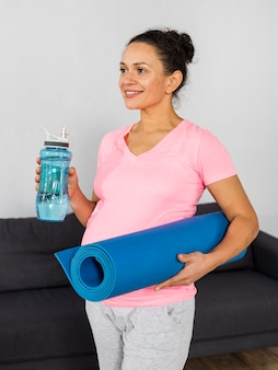Smiley pregnant woman holding water bottle and mat