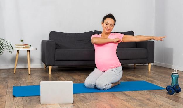 Donna incinta di smiley a casa che si esercita sulla stuoia con il computer portatile