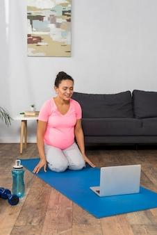 Donna incinta di smiley a casa che si esercita con il computer portatile