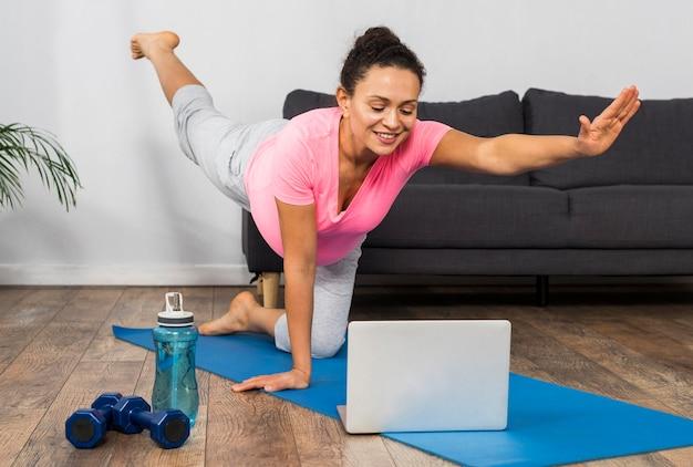 Donna incinta di smiley a casa che esercita yoga con il computer portatile