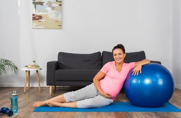 Donna incinta di smiley a casa con la palla e la stuoia di esercizio