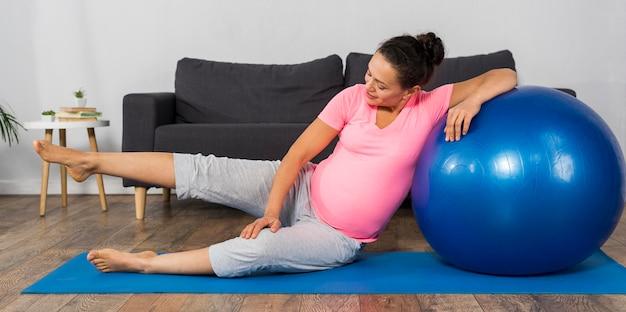 Donna incinta di smiley a casa con palla ginnica e tappetino