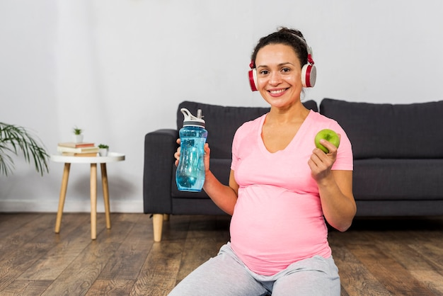Smiley pregnant woman listening to music on headphones while holding apple and water bottle