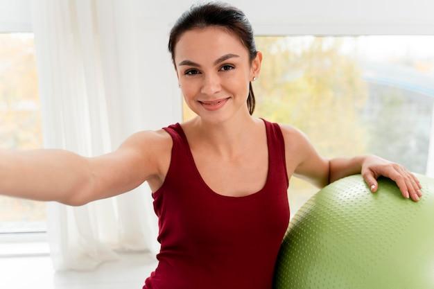 Donna incinta smiley prendendo un selfie accanto a una palla fitness