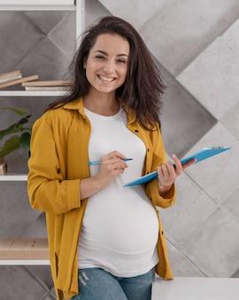 Donna incinta di smiley che lavora da casa con appunti e penna