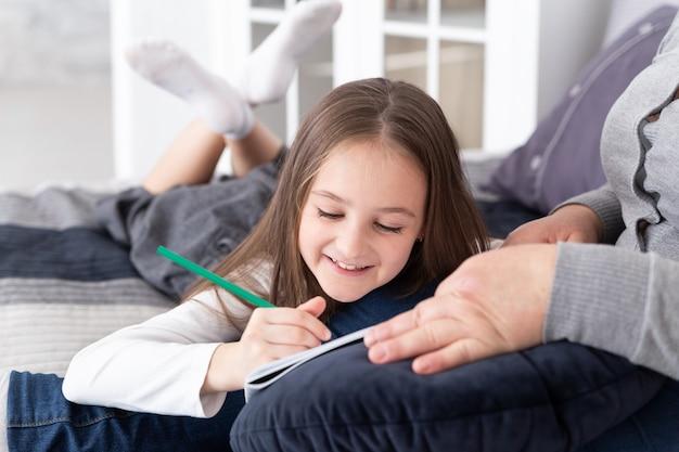スマイリーのプレティーンの女の子が祖母の膝の上に横たわっている間に紙に絵を描きます。