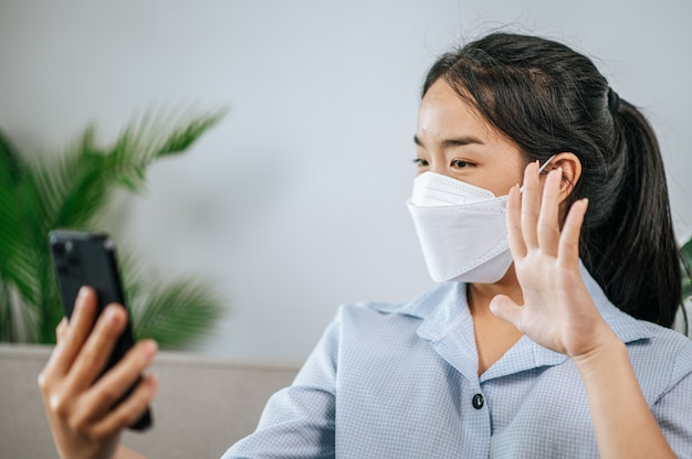 Smiley pretty teenage in face mask sitting on sofa and use smartphone to video call or selfie,  during quarantine covid-19 self isolation at home