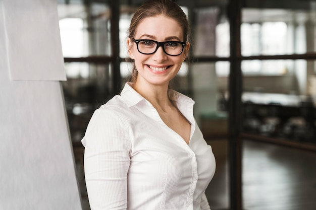 Smiley professional businesswoman with glasses during a presentation