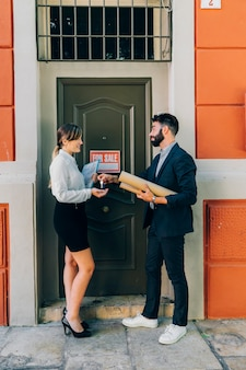 Smiley real estate agents exchanging keys
