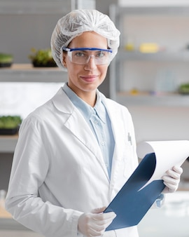 Smiley researcher with clipboard in the biotechnology laboratory