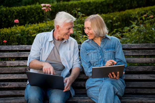 Smiley senior couple outdoors on bench with laptop and tablet