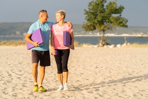 Smiley senior couple with working out equipment on the beach and copy space