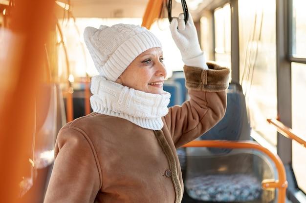 Smiley senior female riding bus
