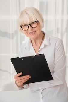 Smiley senior holding a clipboard