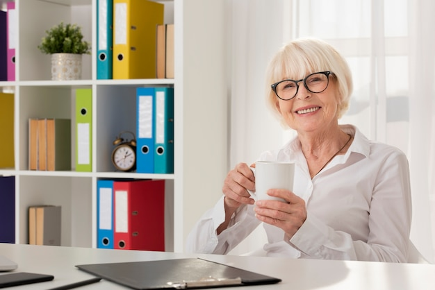 Smiley senior holding a cup in her office