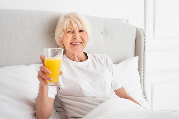 Smiley senior holding a glass with juice
