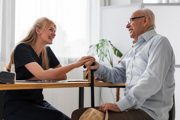 Smiley senior man conversing with nurse
