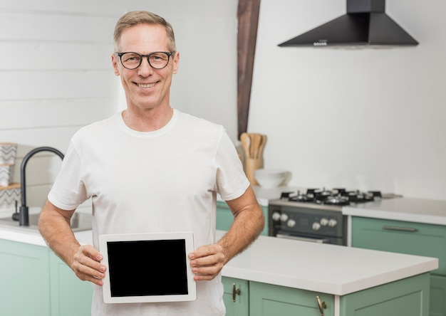 Smiley senior man holding an empty tablet
