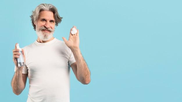 Uomo senior di smiley che usando detergente