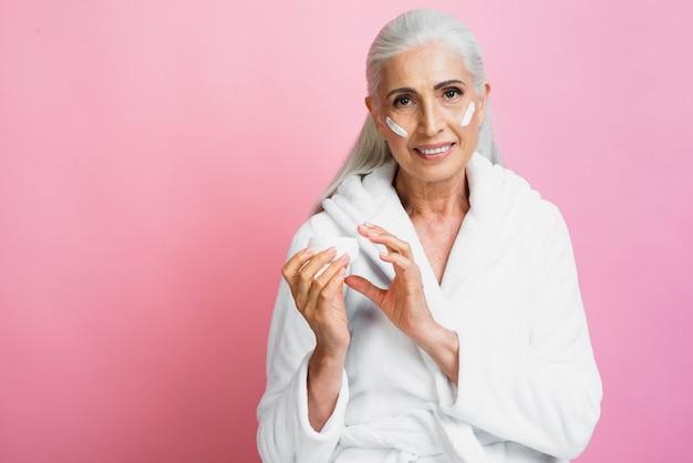 Smiley senior woman applying moisturizer