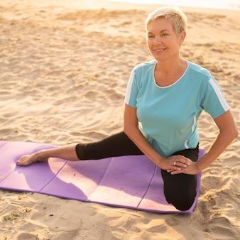 Donna maggiore di smiley che fa yoga sulla spiaggia