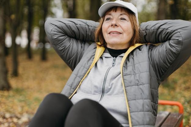 屋外で運動するスマイリー年配の女性