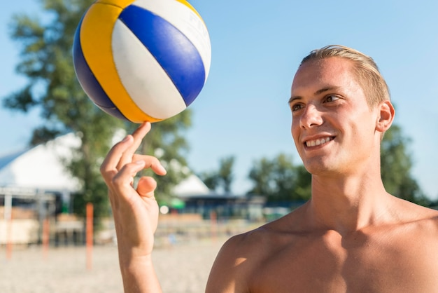 Smiley shirtless male volleyball player holding ball with finger