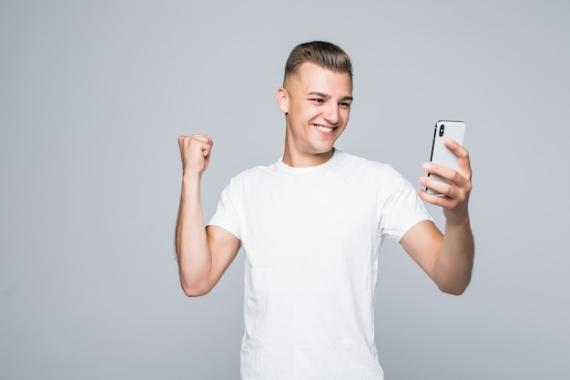 Il giovane forte di smiley indossa una maglietta bianca e fa un selfie con uno smartphone d'argento.