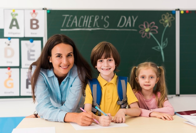 Insegnante di smiley che aiuta gli studenti in classe