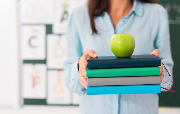 Смайлик учитель держит кучу книг и яблоко