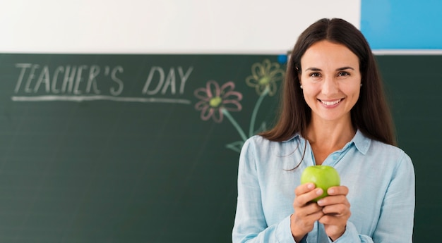 Smiley teacher holding an apple with copy space