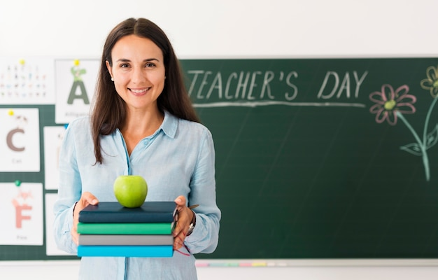 Smiley teacher holding a bunch of books and an apple with copy space