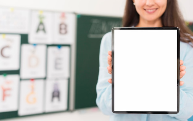 Smiley teacher holding an empty screen tablet