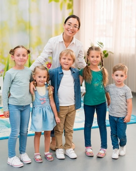 Учительница-смайлик держит своих учеников для фото
