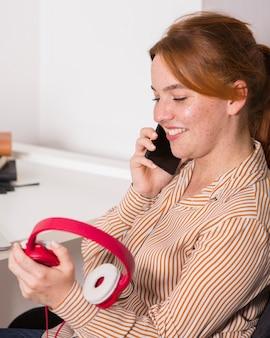 Учитель-смайлик разговаривает по смартфону и держит наушники во время онлайн-класса