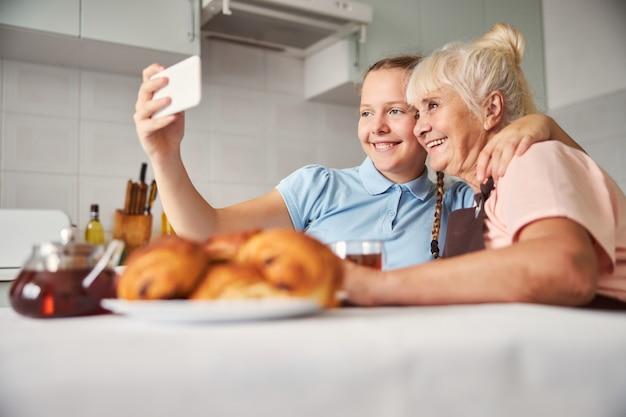 사랑하는 할머니와 셀카를 찍는 웃는 십대 소녀