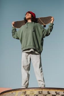 Улыбающийся подросток в скейтпарке развлекается со скейтбордом