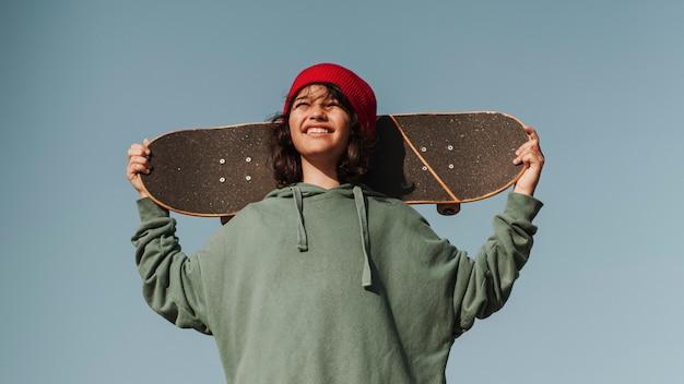 Улыбающийся подросток в скейтпарке развлекается