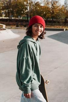 Улыбающийся подросток со скейтбордом в парке