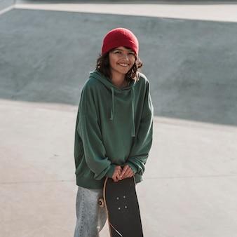 スケートパークでスケートボードを持ったスマイリーティーンエイジャー