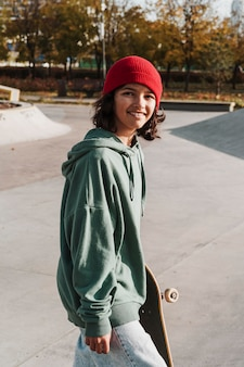 Smiley teenager with skateboard at the park
