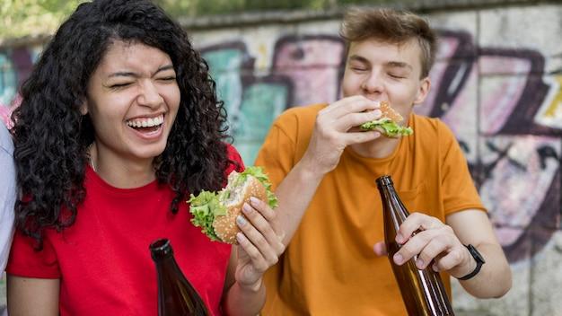 Улыбающиеся подростки едят гамбургеры на открытом воздухе с напитком