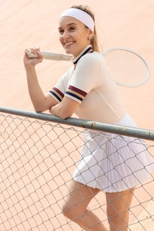 Smiley tennis player standing with racket on shoulder